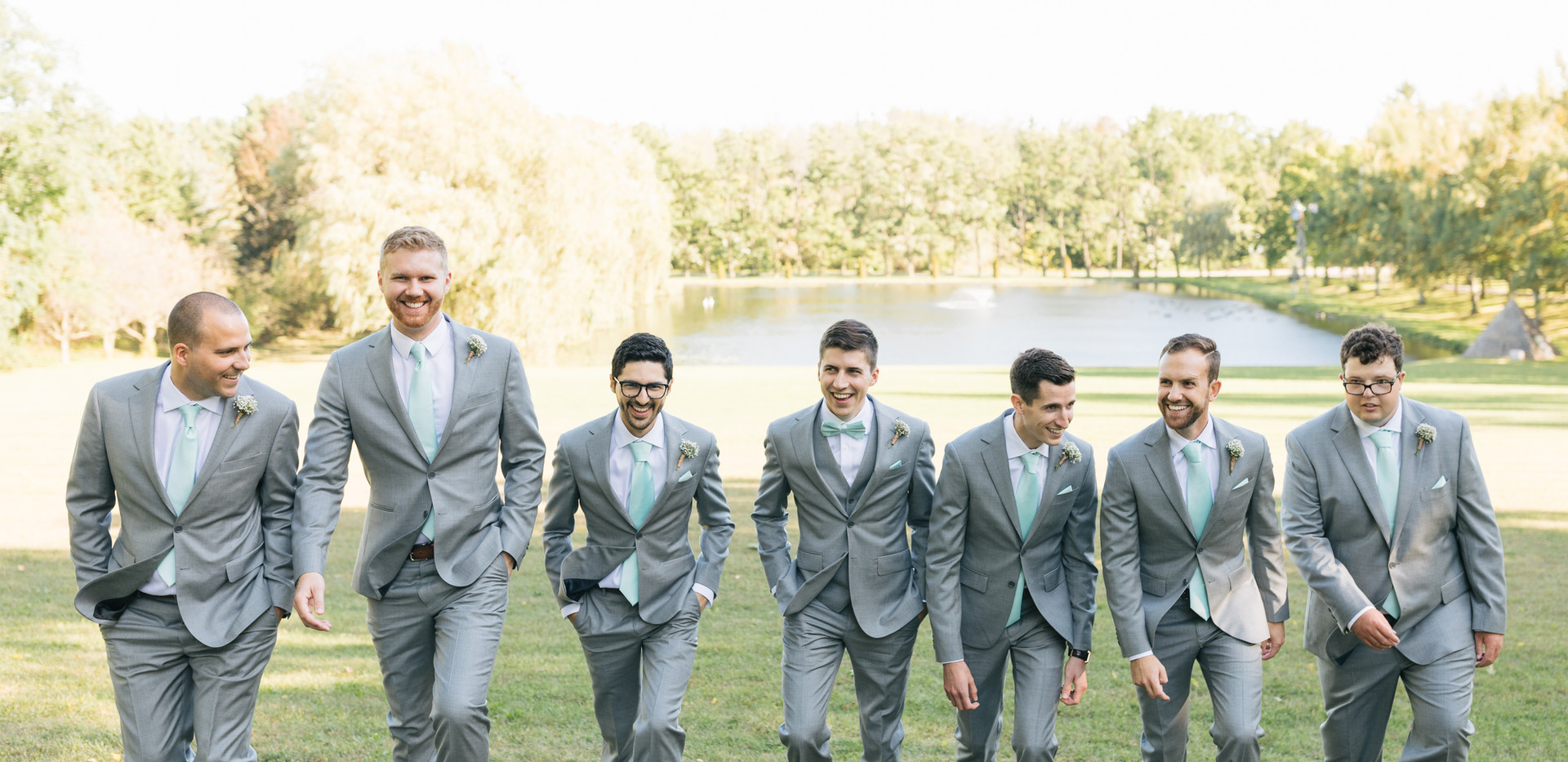 close up of groomsmen walking towards camera with private pond in background