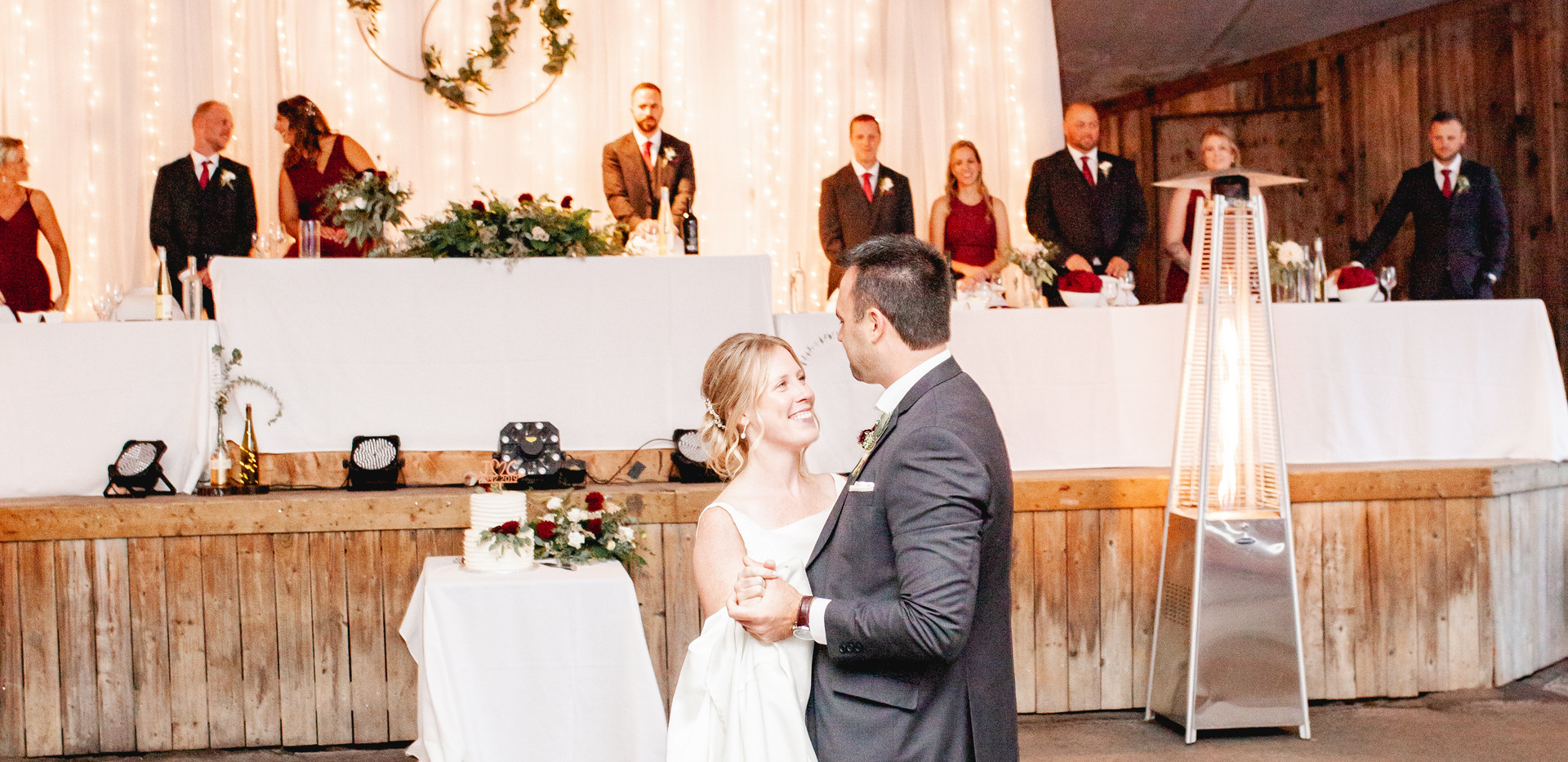 bride and groom sharing their first dance in front of Refined Rustic Glam Head Table on stage with twinkling lights and white sheer backdrop