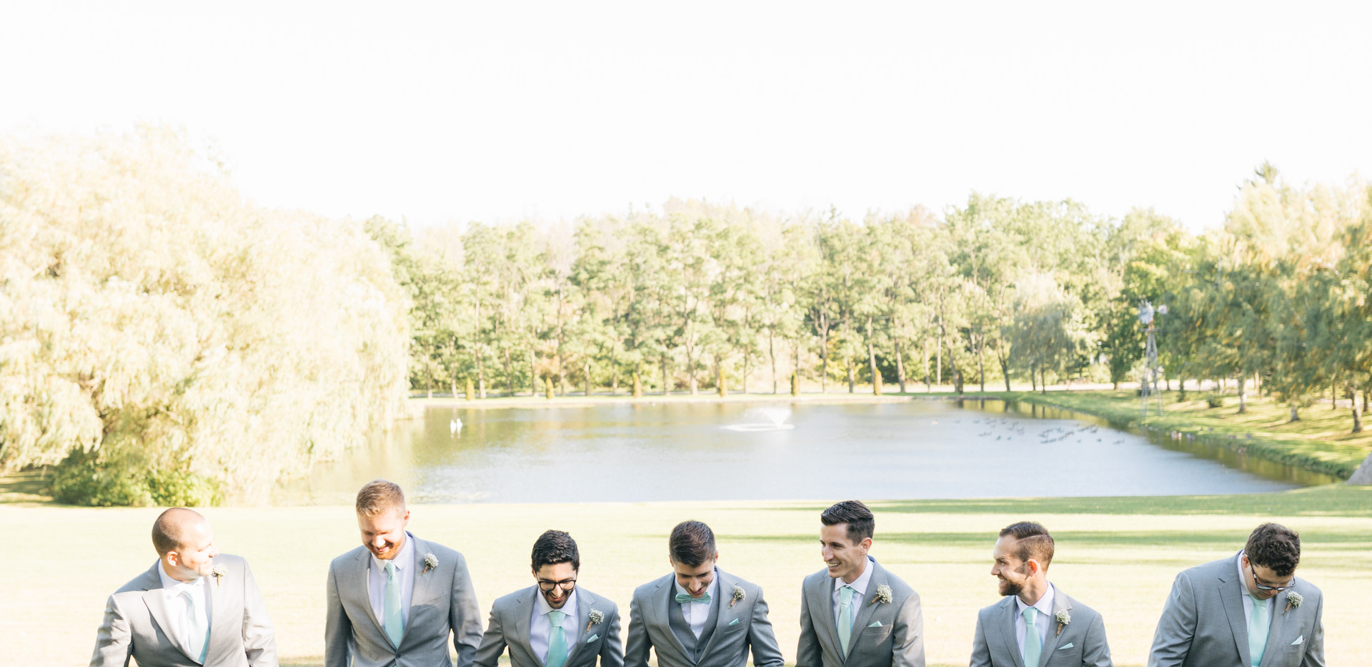 Groomsmen walking towards camera with pond in the background