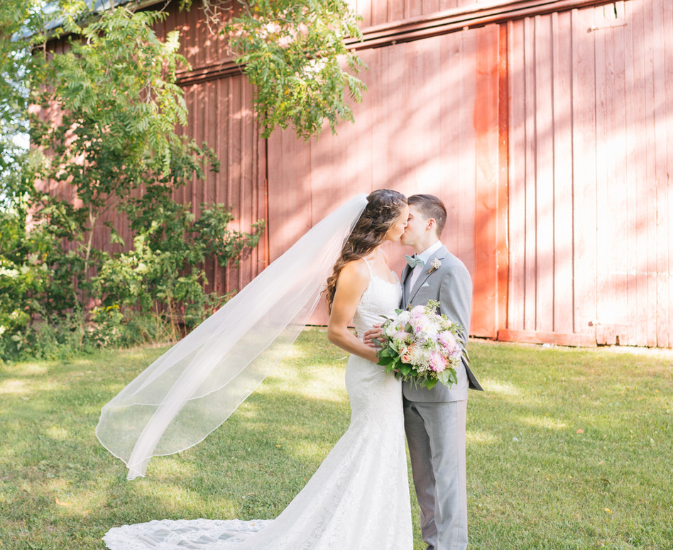 bride and groom kissing in front of red barn with veil blowing in the wind