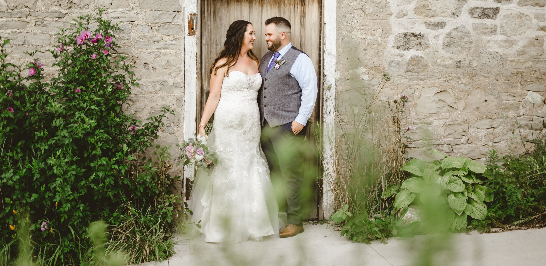Bride and Groom posing along exterior wall of white stone barn