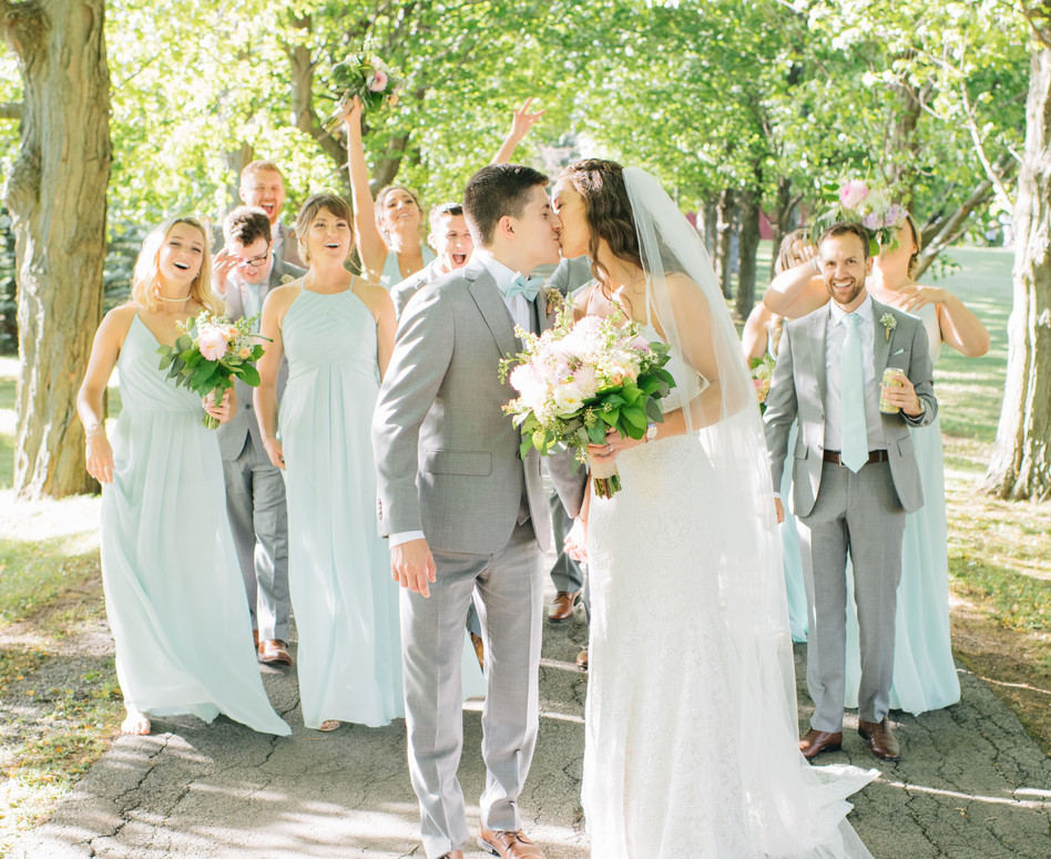 wedding party walking up private farm laneway, bride and groom kissing in front of group