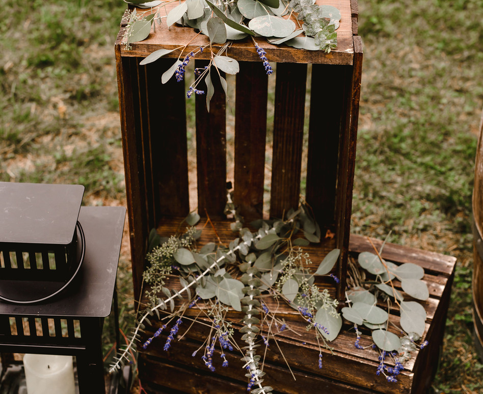 wide shot of decor accessories at ceremony arch, loose varieties of eucalyptus and dried lavender nestled on top