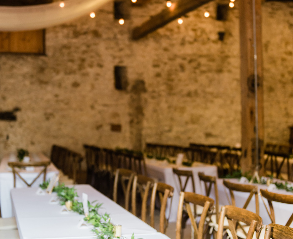 elegant cambridge barn wedding reception space with greenery garlands, gold accents and vineyard chairs