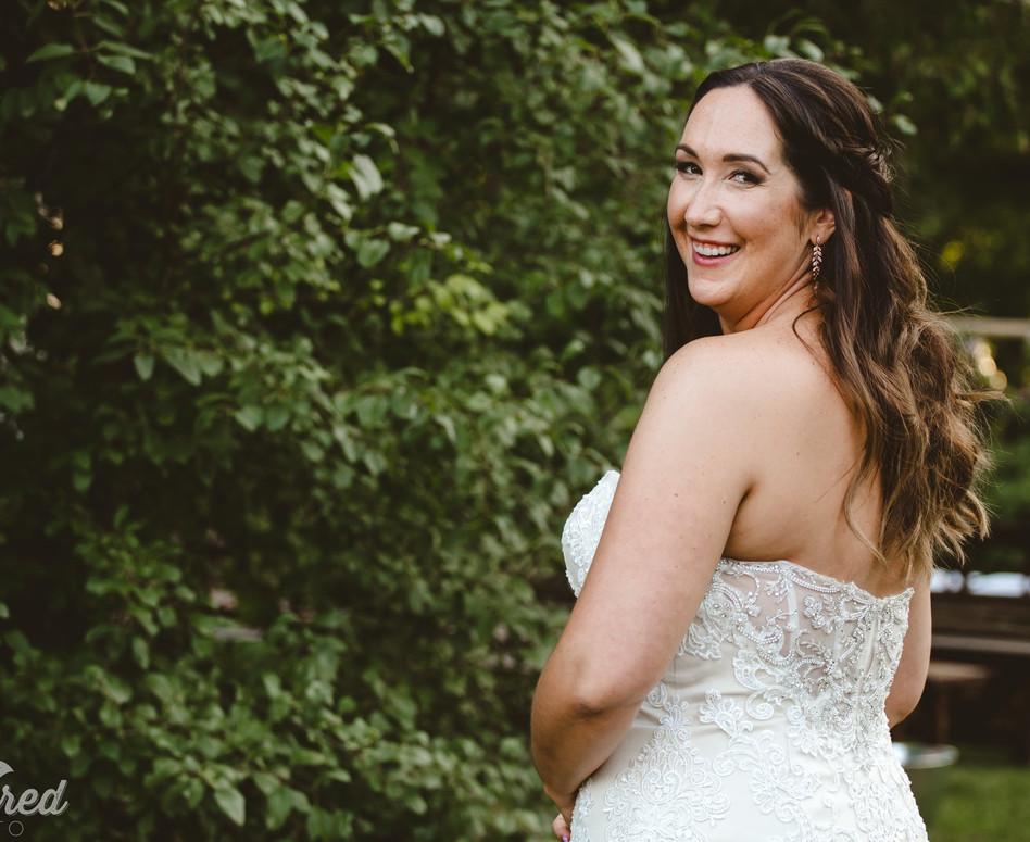 Bride looking back over her shoulder along ceremony path