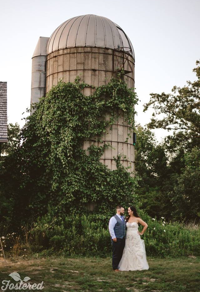 Bride and groom posing in front of white stone barn with silo