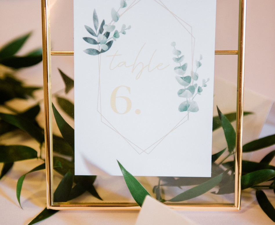 close up shot of gold geometric framed table number with elegant greenery stationery design