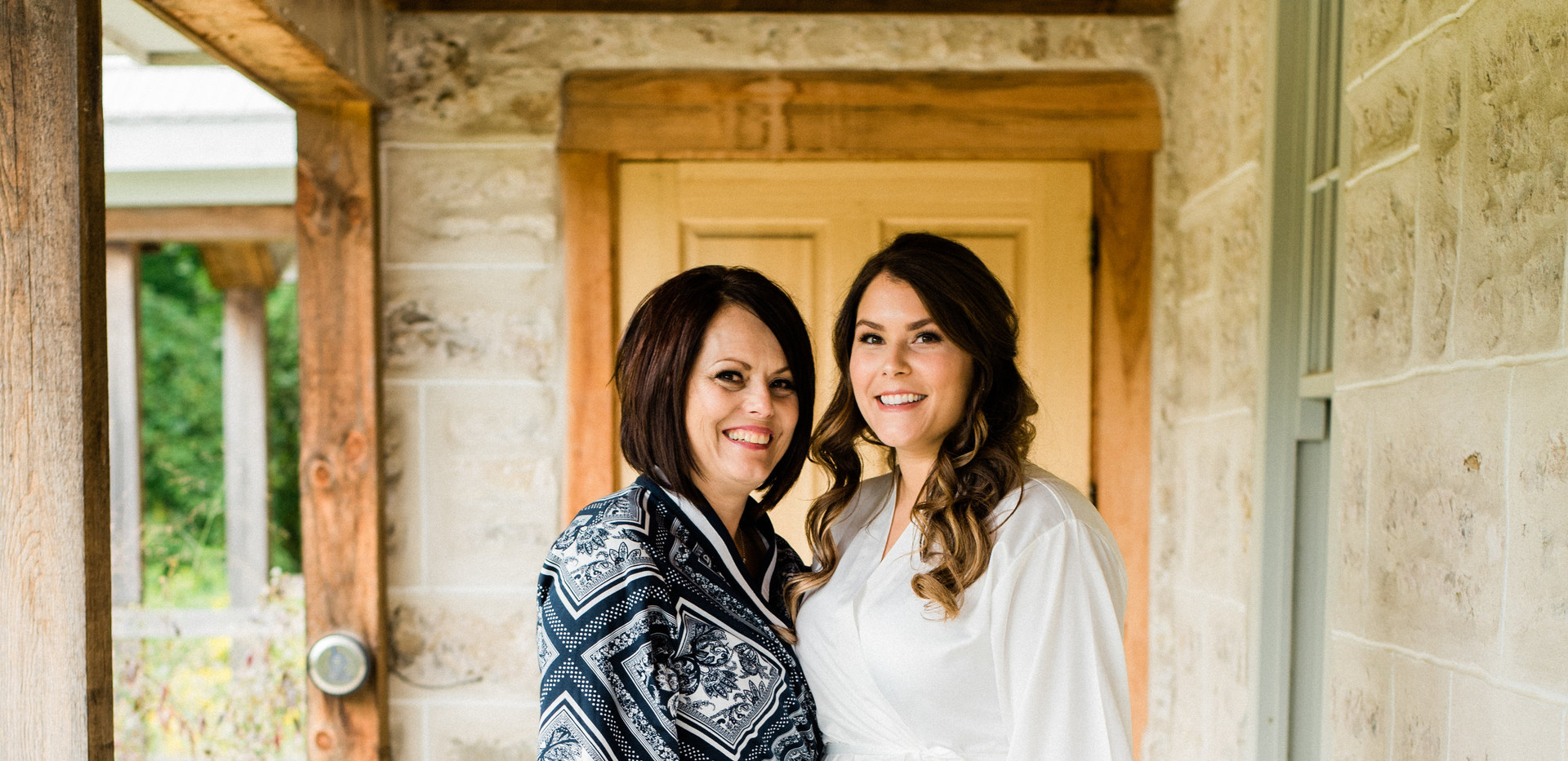 bride and mother of the bride in robes standing on wrap around farmhouse porch
