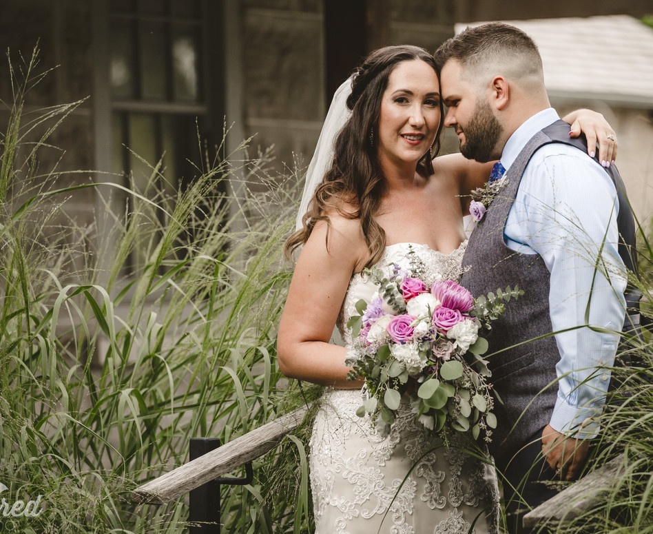 focused shot of Bride and Groom standing among long grass in front of farmhouse
