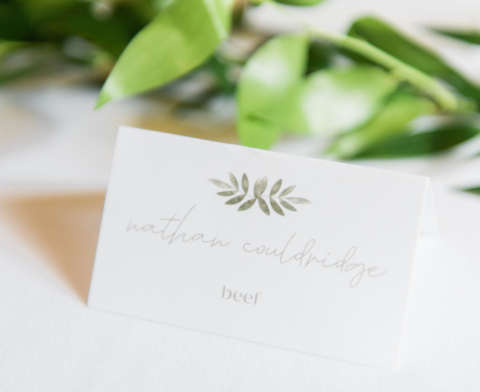 close up of guest place card with modern minimalist greenery theme design, guest name, and meal choice at the bottom