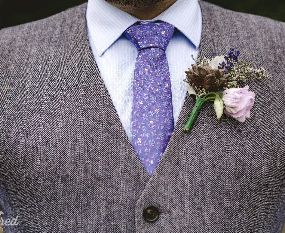 Close up details shot of groom wearing tweed vest, lavender tie and textured lavender boutonniere