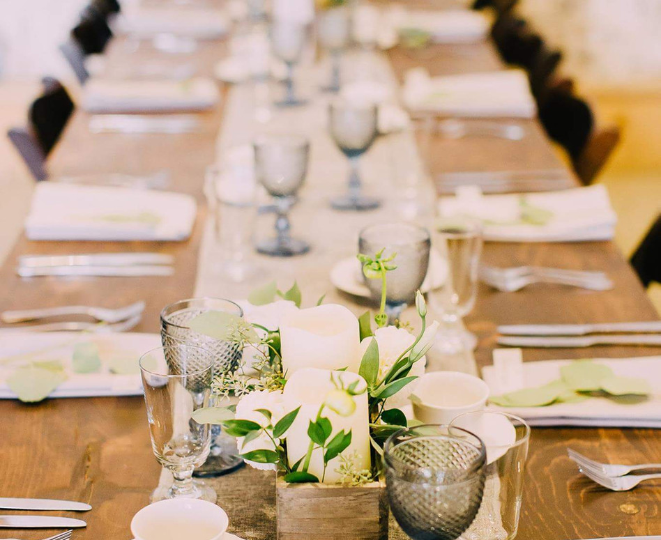 Harvest Table topped with grey linen runner, blue vintage goblets, rustic floral candle box centerpieces