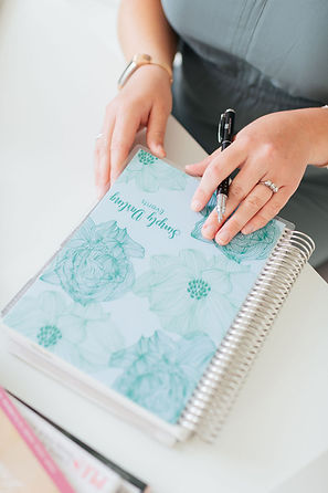Close Up of Wedding Planner placing her hands on company branded paper planning agenda book, Amber Stemmler