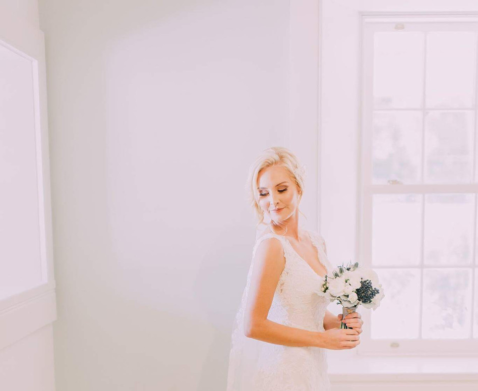 Bride just before walking out to the ceremony, holding bouquet looking over her shoulder