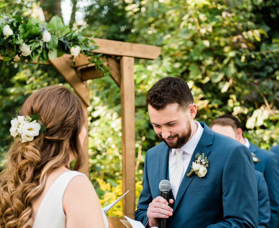 close up of groom saying vows at outdoor forest ceremony