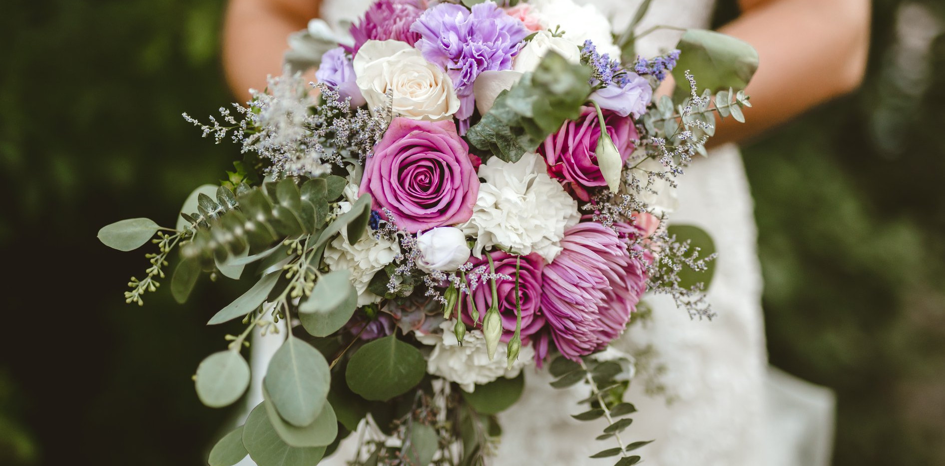 close up of bridal bouquet with variety of eucalyptus, succulents and lavender blooms