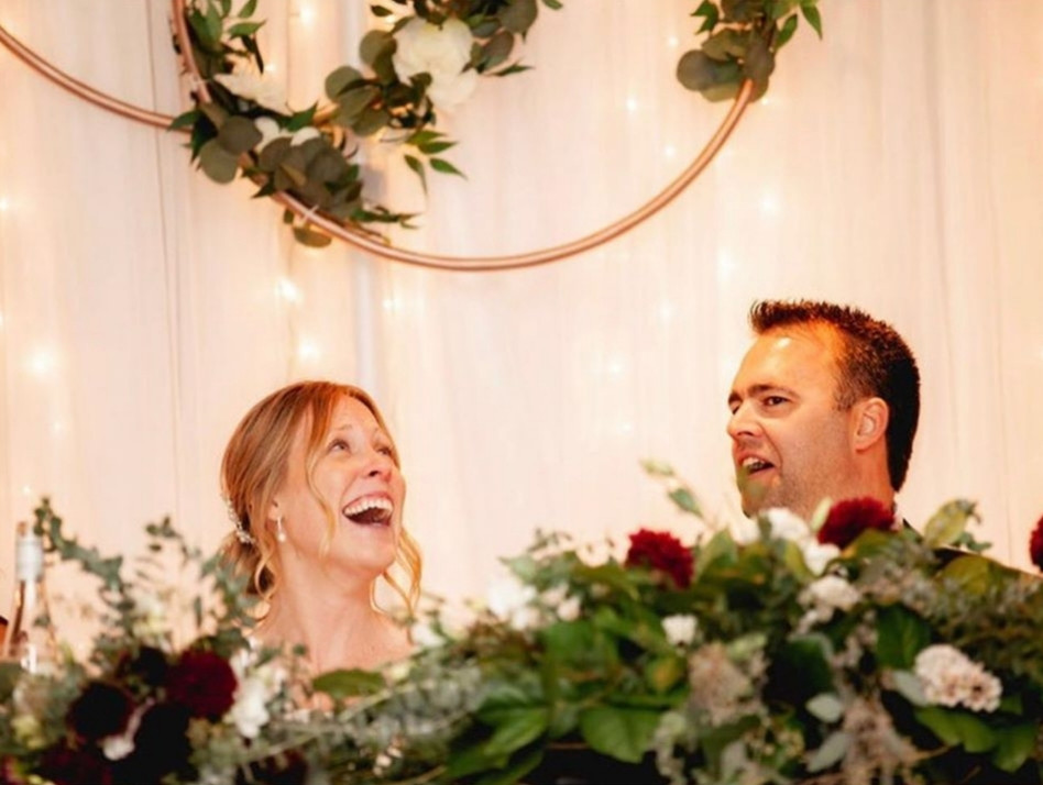 Close up shot of Bride and Groom reacting to a speech while seated at their head table