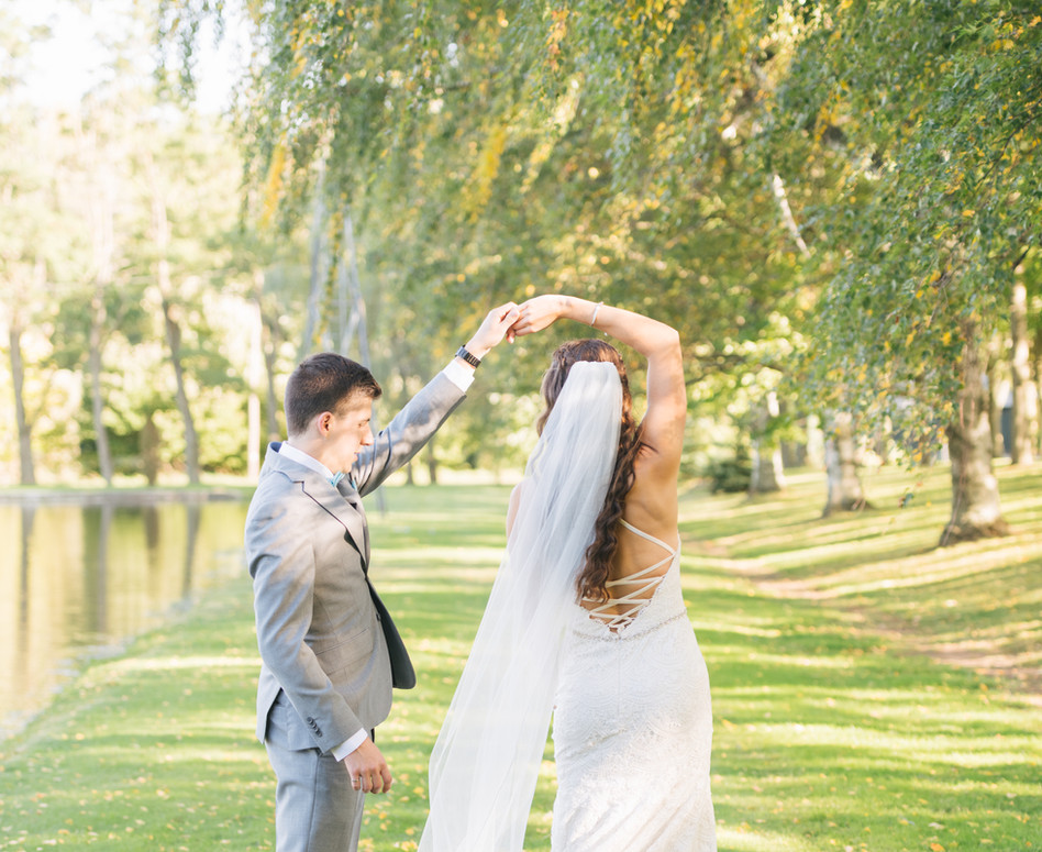Bride and Groom dancing in front of pond