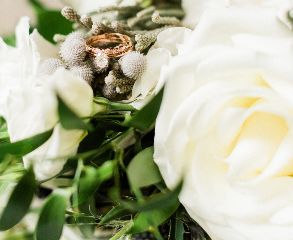 close up shot of rings laying on top of bridal bouquet