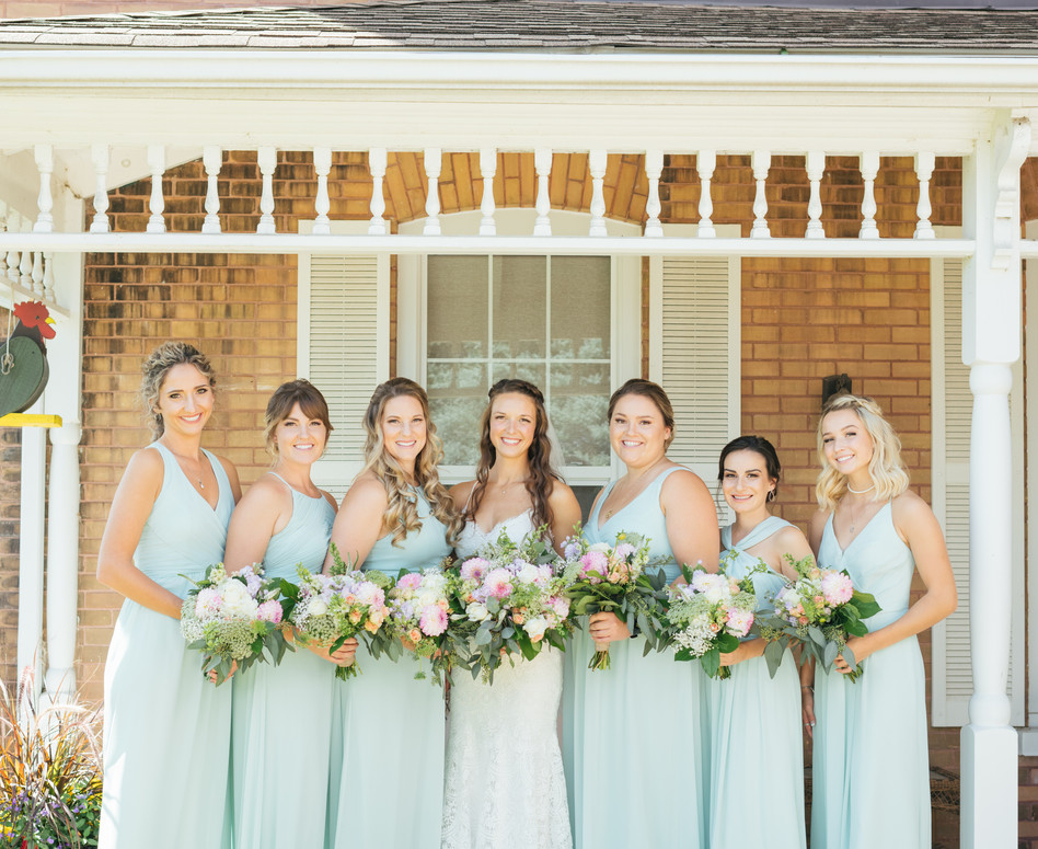bridesmaids in mint dresses with pastel bouquets against red brick farmhouse