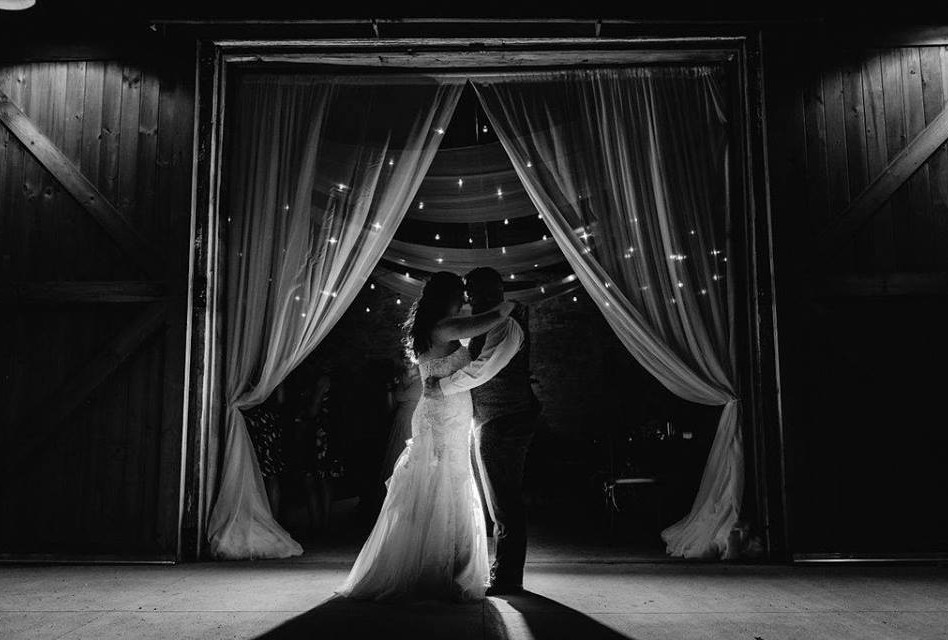 Bride and Groom dancing in front of large barn doors with white sheer curtains and edison bulbs in the background