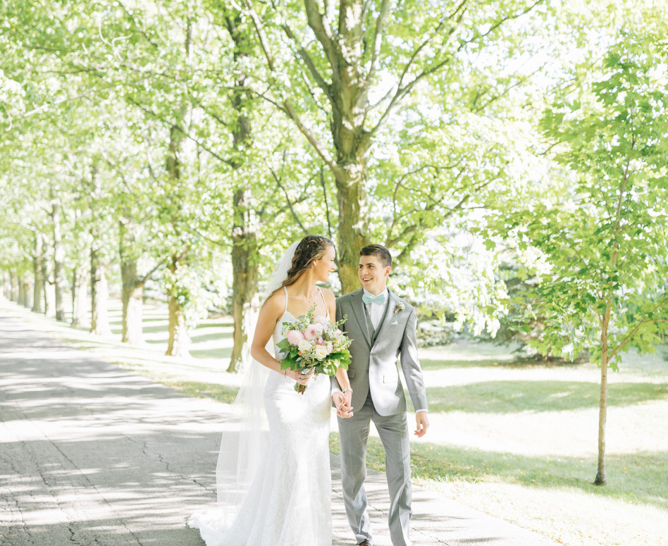 bride and groom walking up private tree lined laneway looking at eachother