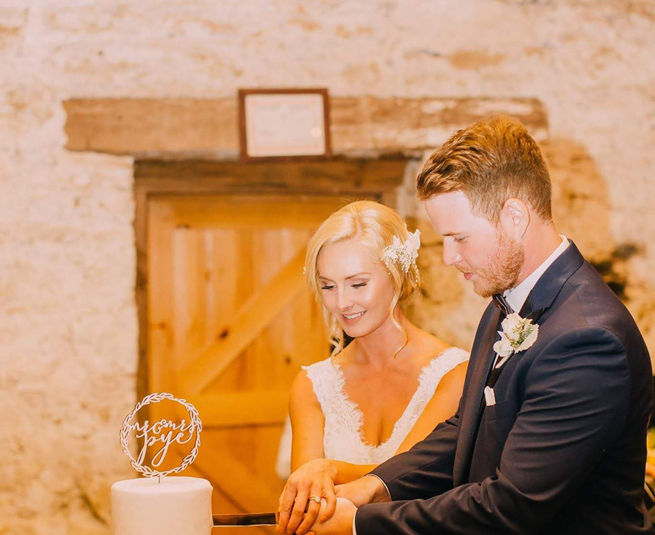 Bride and Groom cutting their classic white 3-tier wedding cake