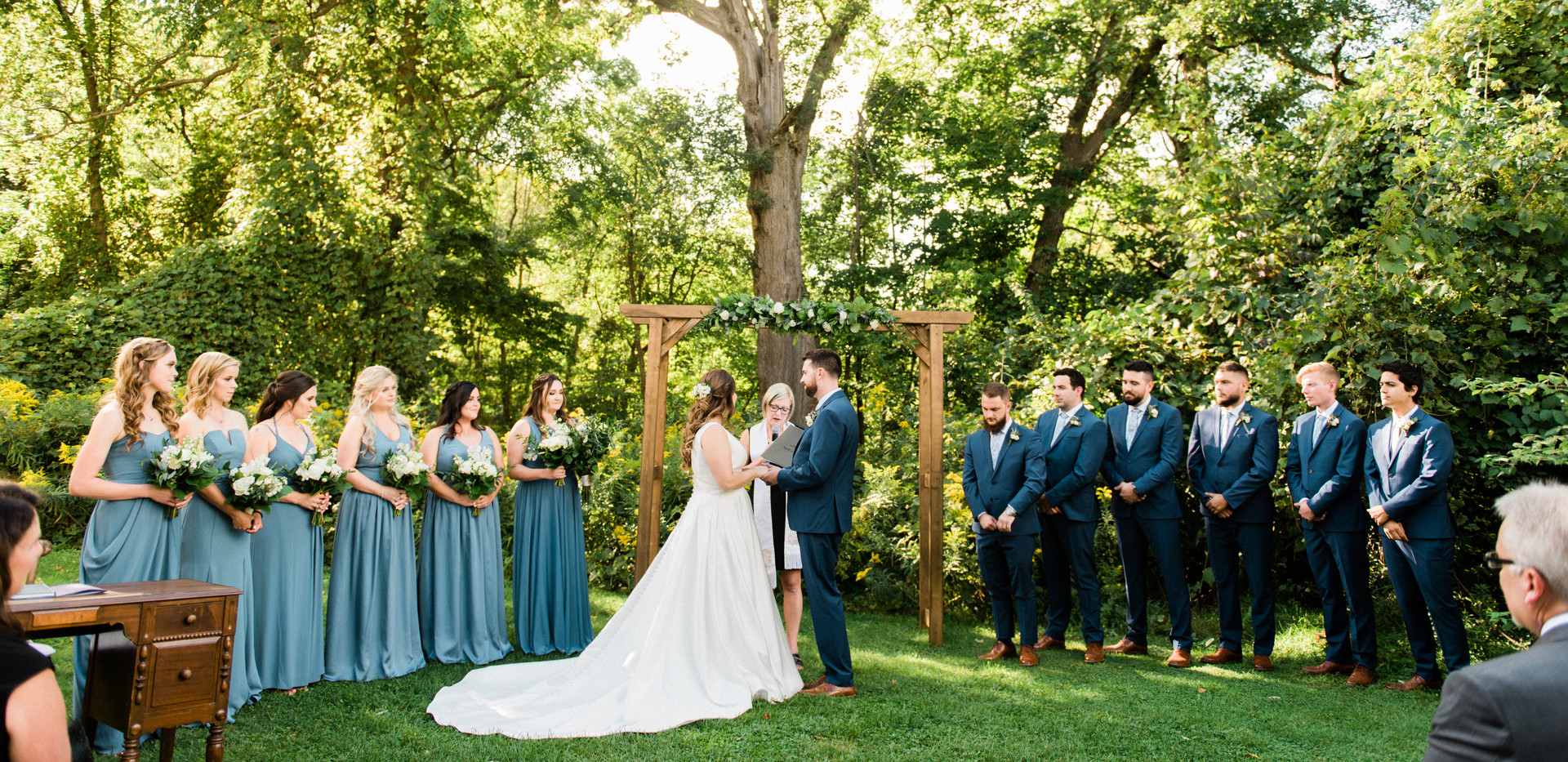 wide shot of whole wedding party standing at arbour for outdoor forest ceremony, bridesmaids wearing dusty blue dresses, groomsmen in dark navy blue suits