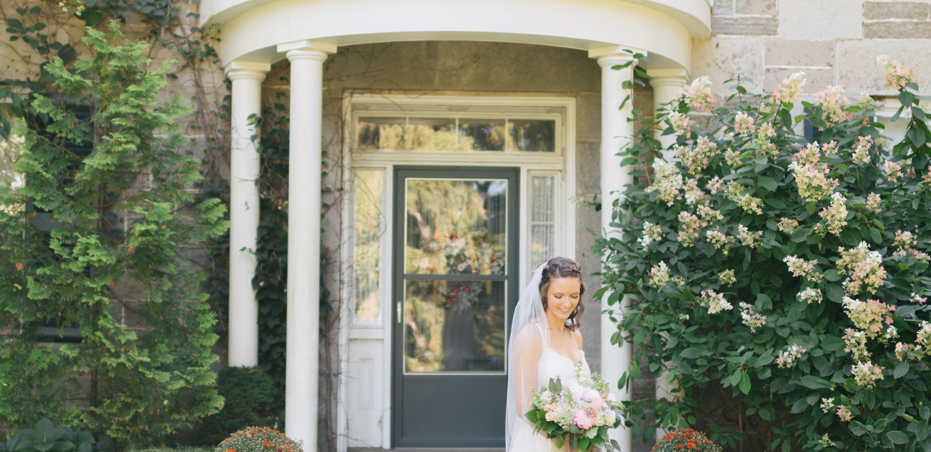 bride standing in front of family farmhouse looking down at pastel bouquet