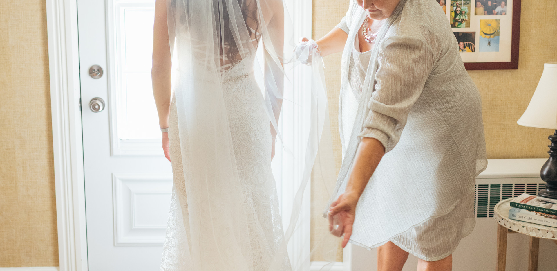 bridal portrait from back with mother adjusting veil over wedding dress