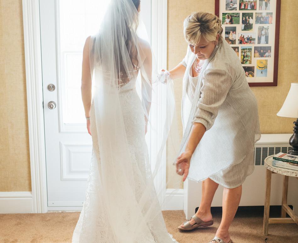 bridal portrait from back with mother adjusting veil over wedding dress