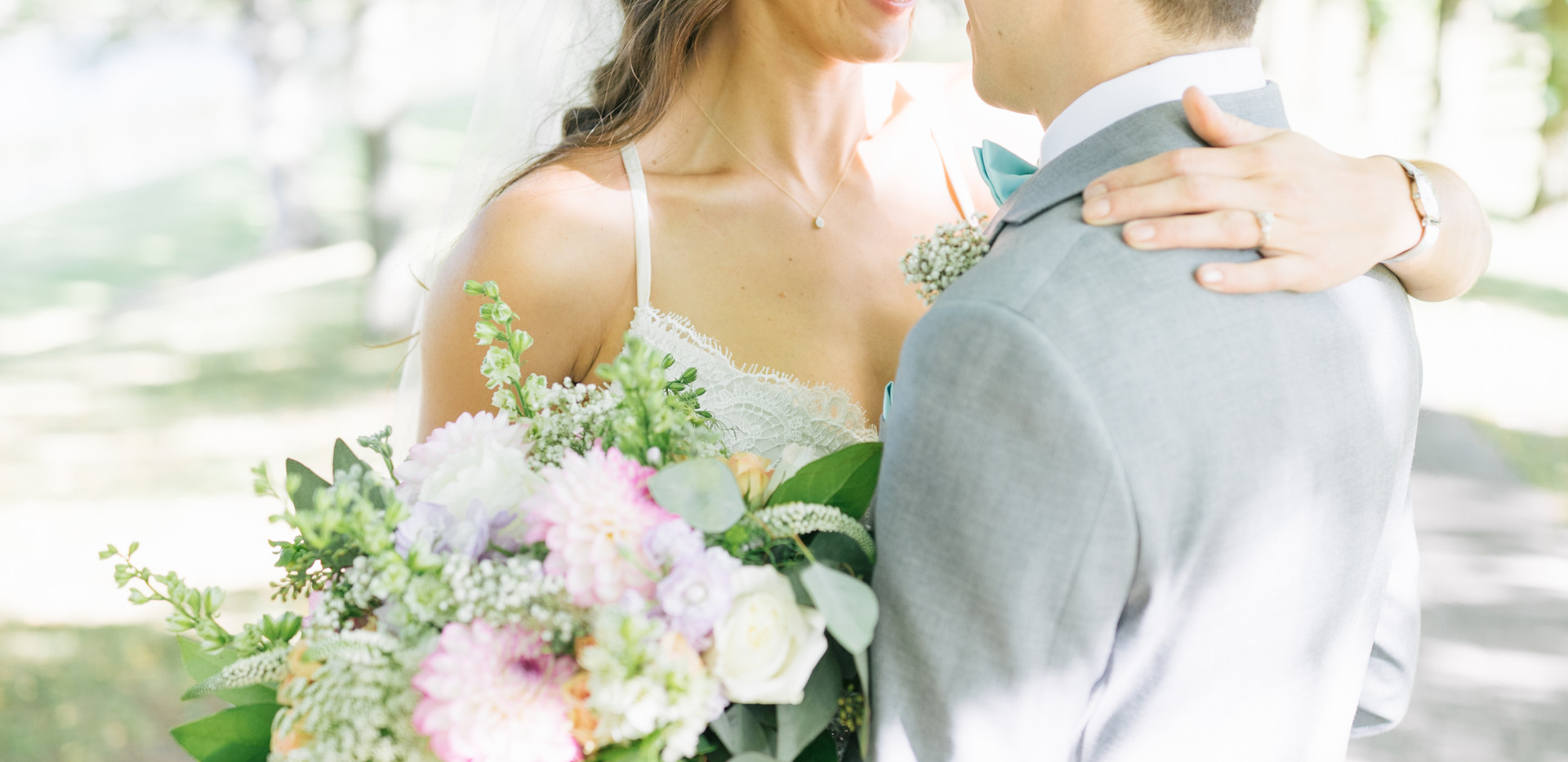 bride and groom smiling at eachother with pastel bouquet held in front