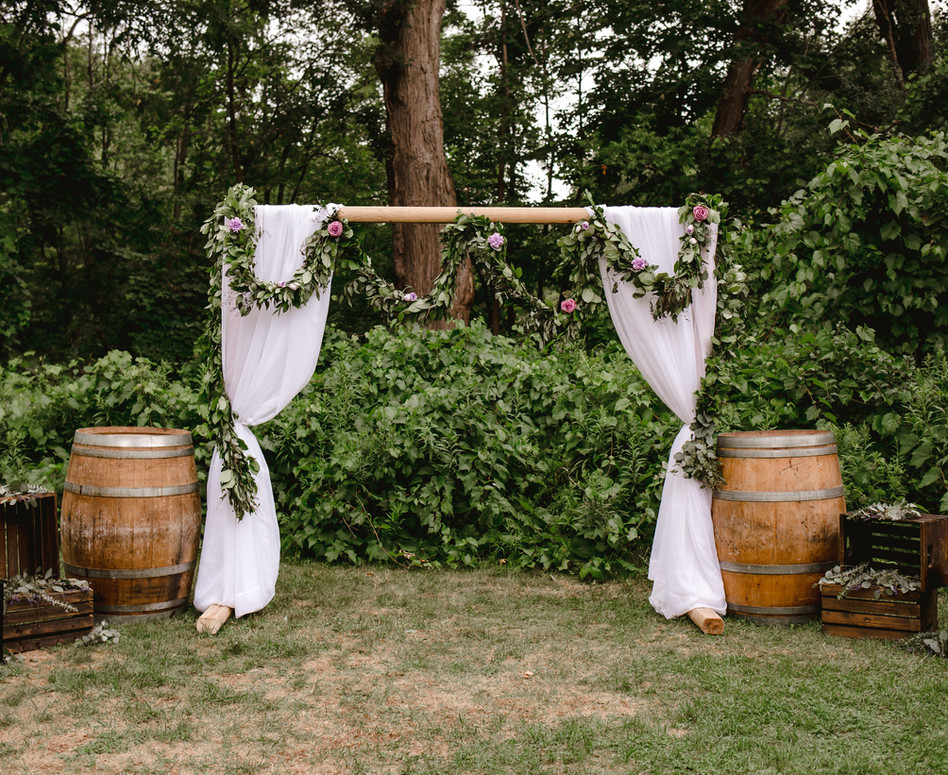 Wide Shot of Outdoor Forest Ceremony Arch with white sheer paneling and greenery/floral garland swagged along wooden arch with wine barrels, wood crates and lanterns on either side