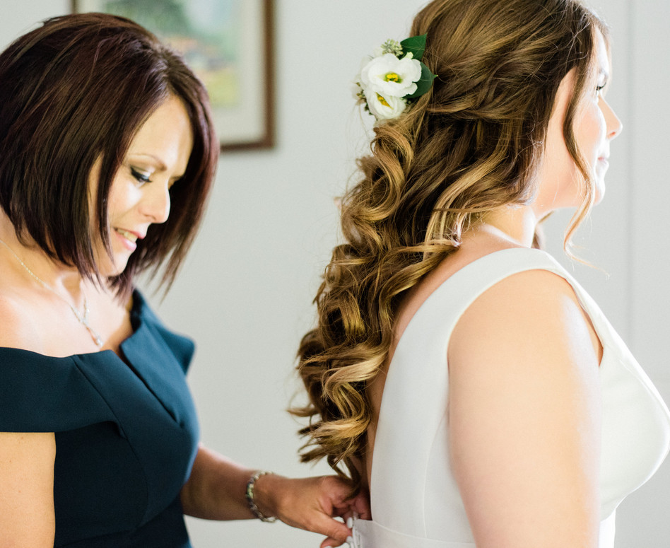 close up of mother of the bride buttoning up wedding dress while bride looks into mirror