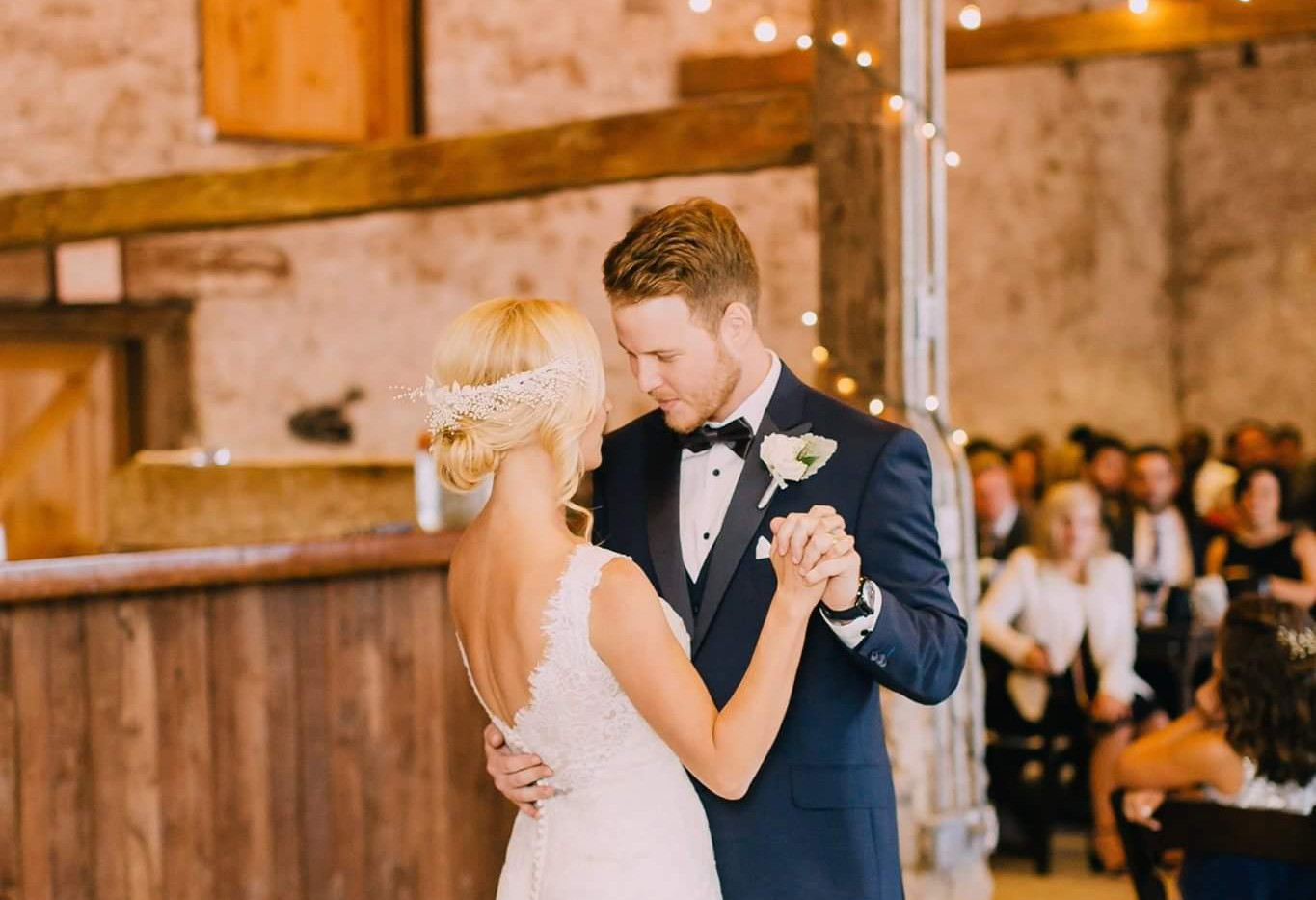 Bride and Groom sharing their first dance in white stone barn under espresso cafe lighting