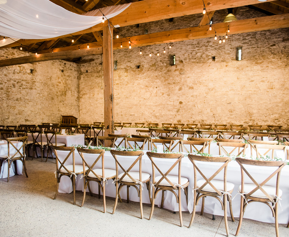 wide shot of white stone barn reception space with white ceiling draping, vineyard chairs