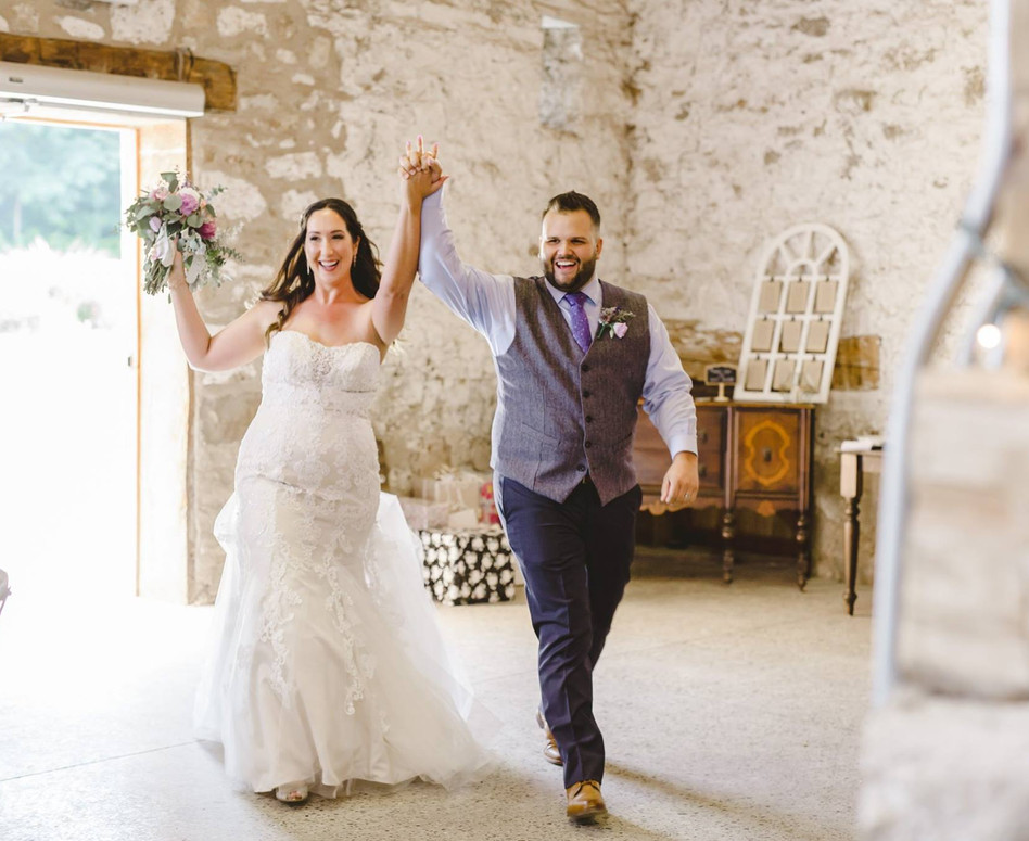 Bride and groom doing their grand entrance into the white stone barn reception in Cambridge, Ontario