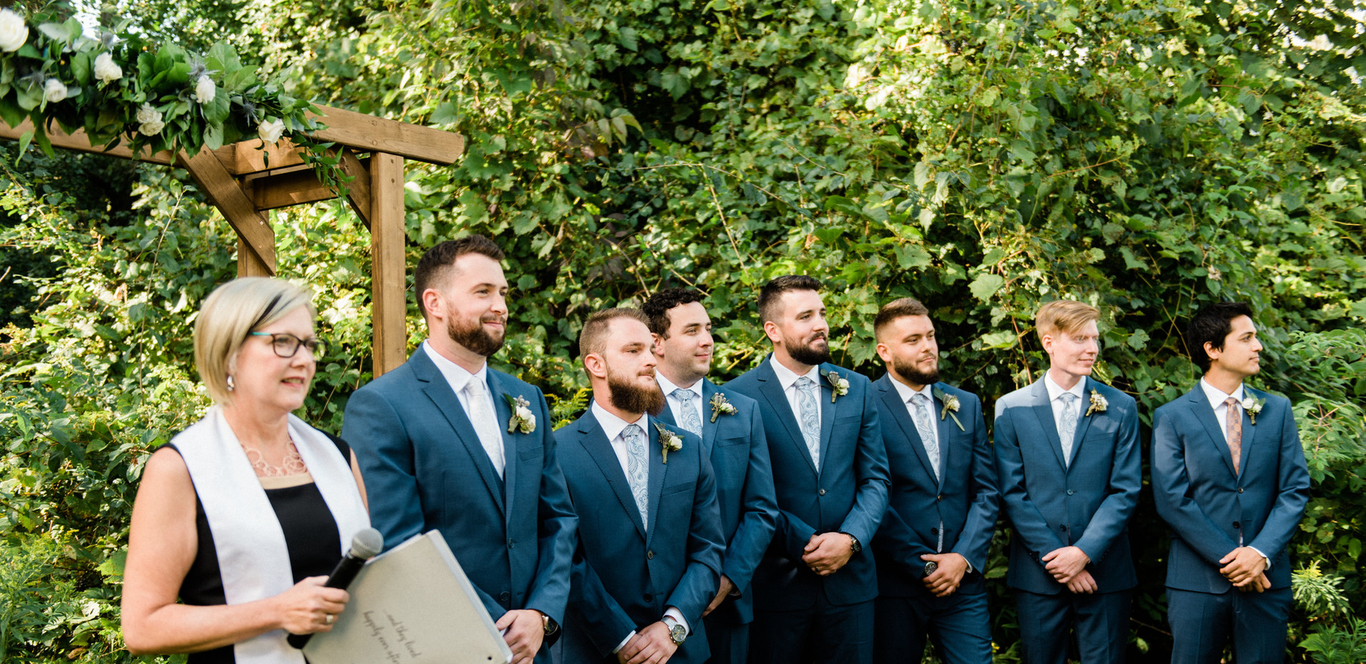 officiant standing at outdoor forest ceremony with groom and groomsmen lined up waiting for bride to come down aisle
