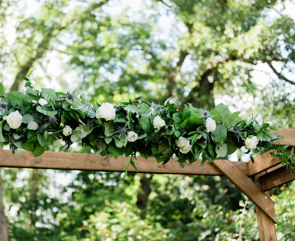 close up of lush white wild greenery arrangement on top of ceremony arbour