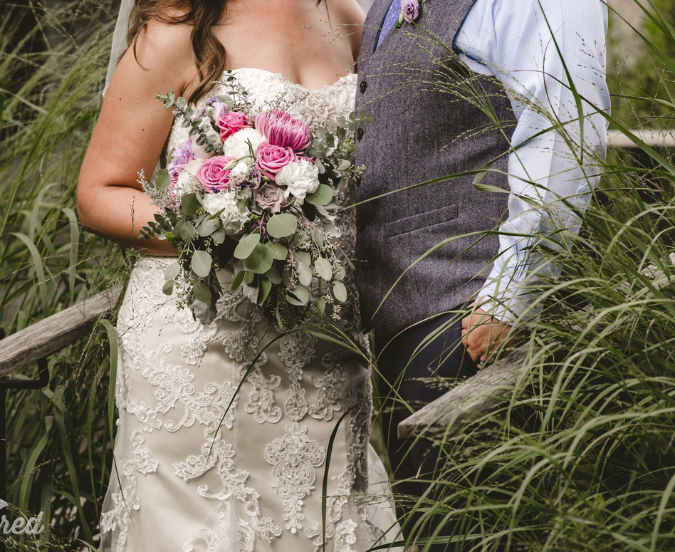 Close up of bride and groom from the necks down with focus on bridal bouquet with variety of eucalyptus, succulents and lavender blooms