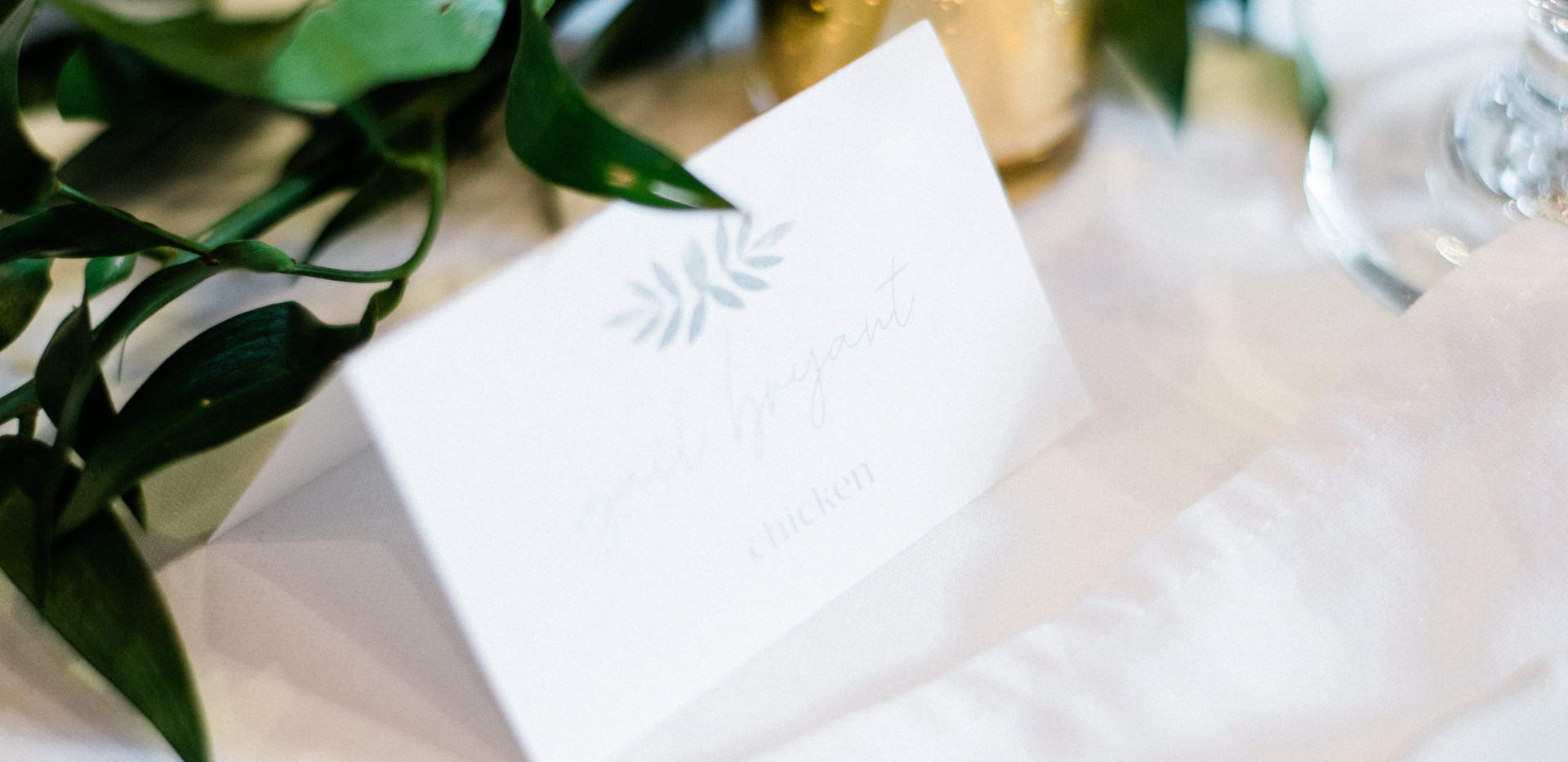 close up of guest table place card with gold candle votive with loose ruscus greenery runner