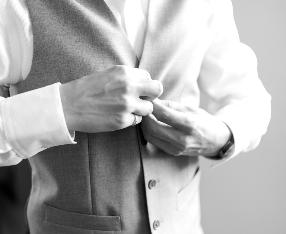 groom buttoning up his suit vest documentary style
