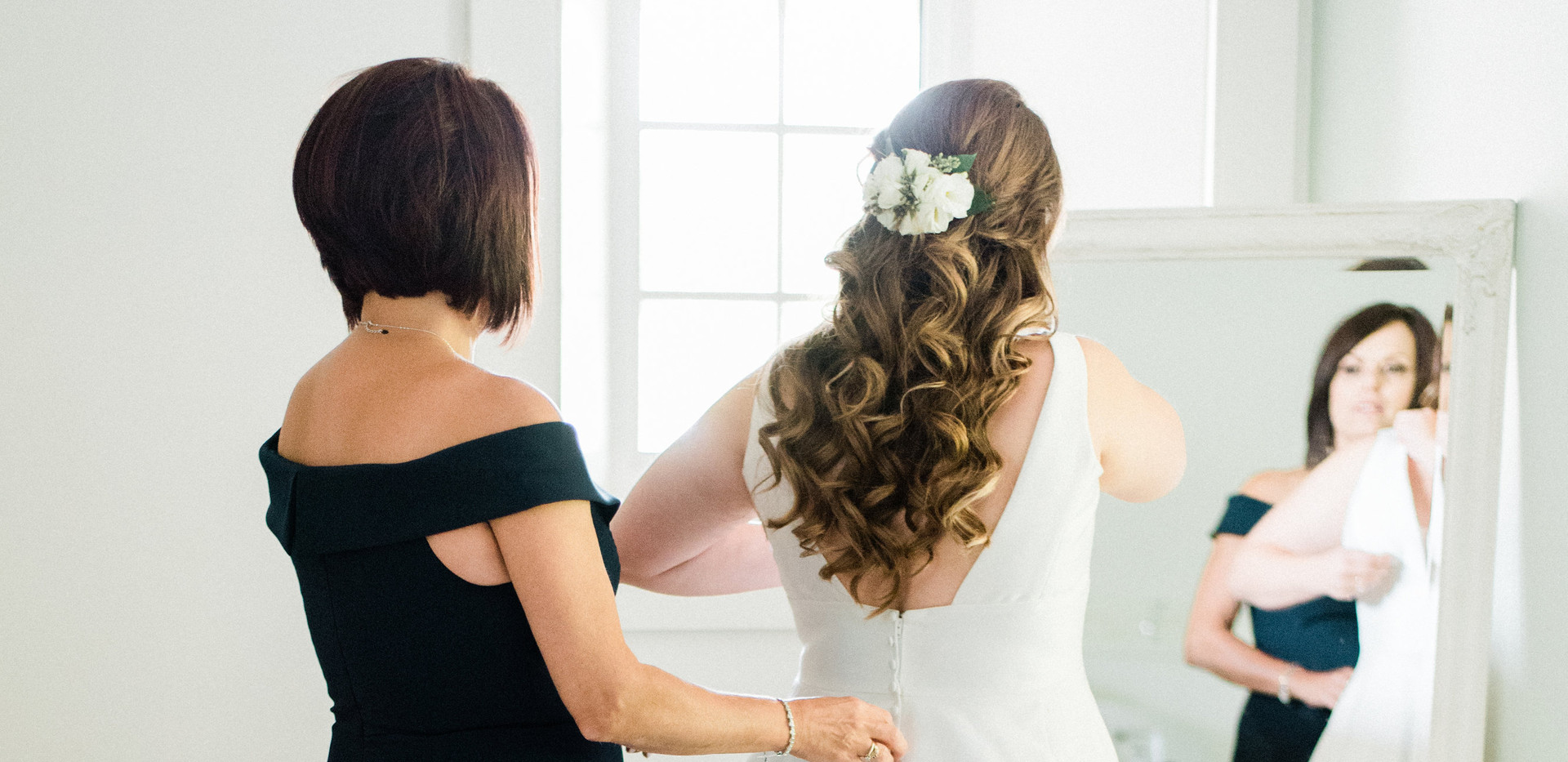 shot from back of bride and mother of the bride looking at full length mirror in bridal suite
