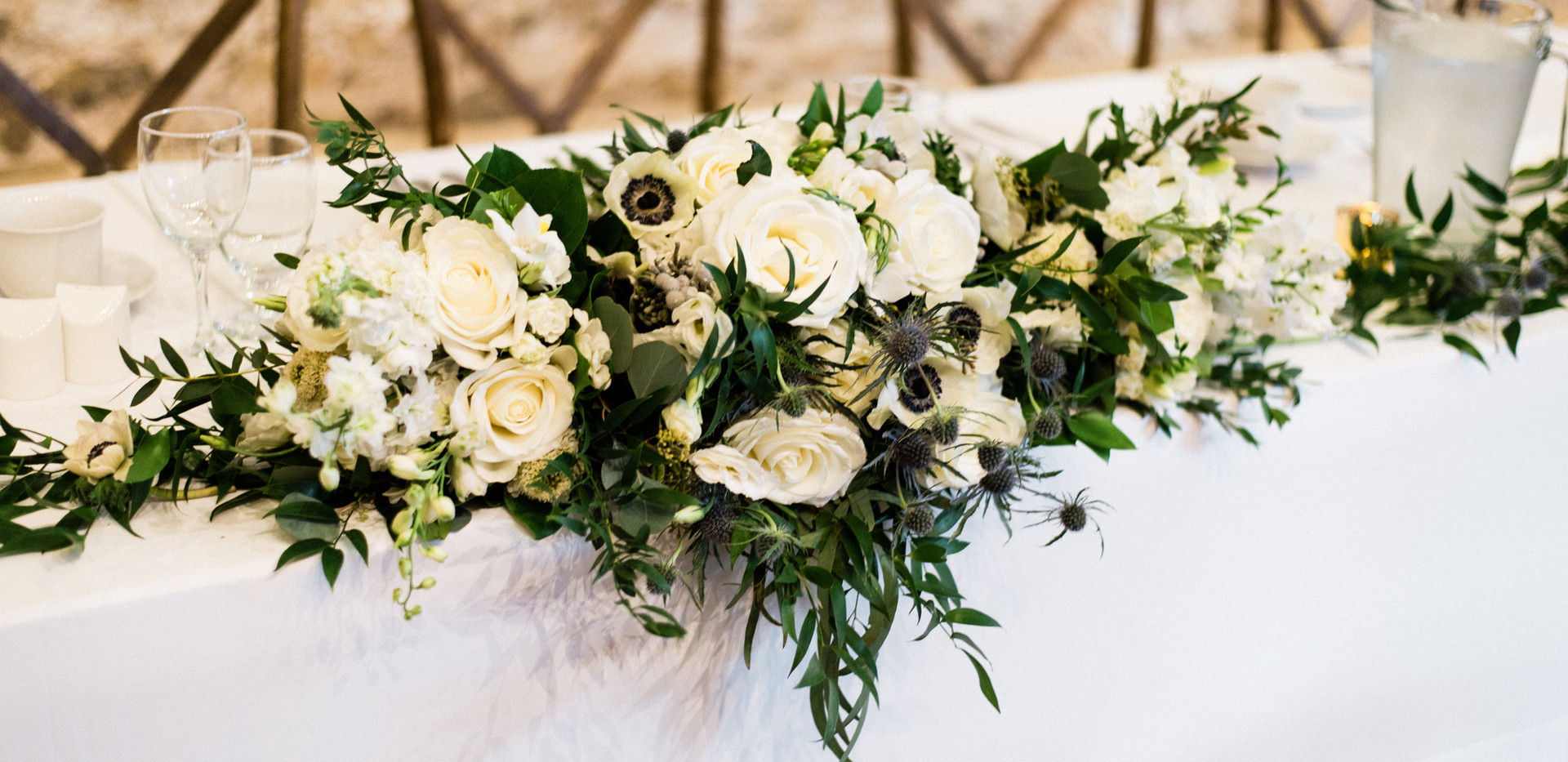 lush white wild greenery bridal bouquet and bridesmaids bouquets laid flat on head table to make one large arrangement