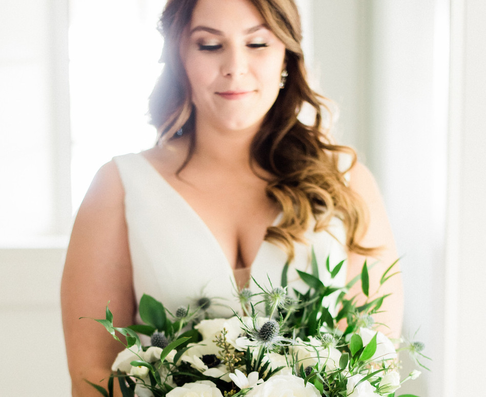 bride holding her lush white wild greenery bouquet with anemones and blue thistles