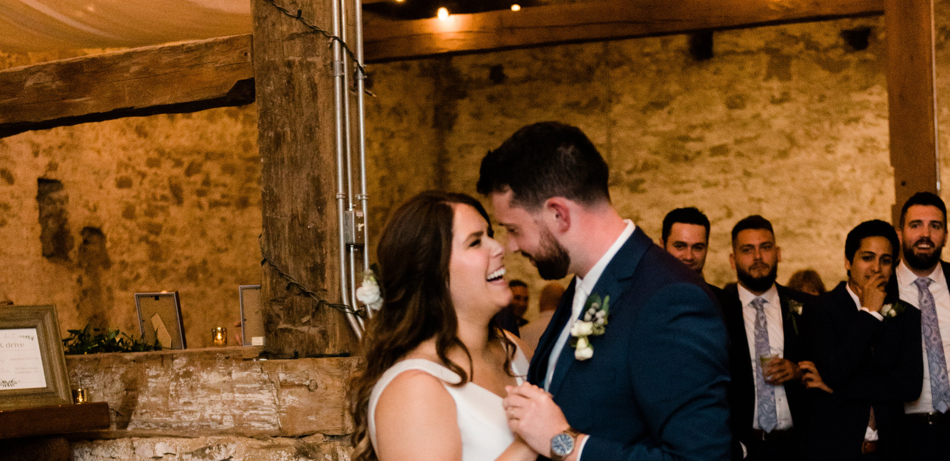 wide shot of bride and groom laughing during their first dance under white draping and espresso bulb lighting