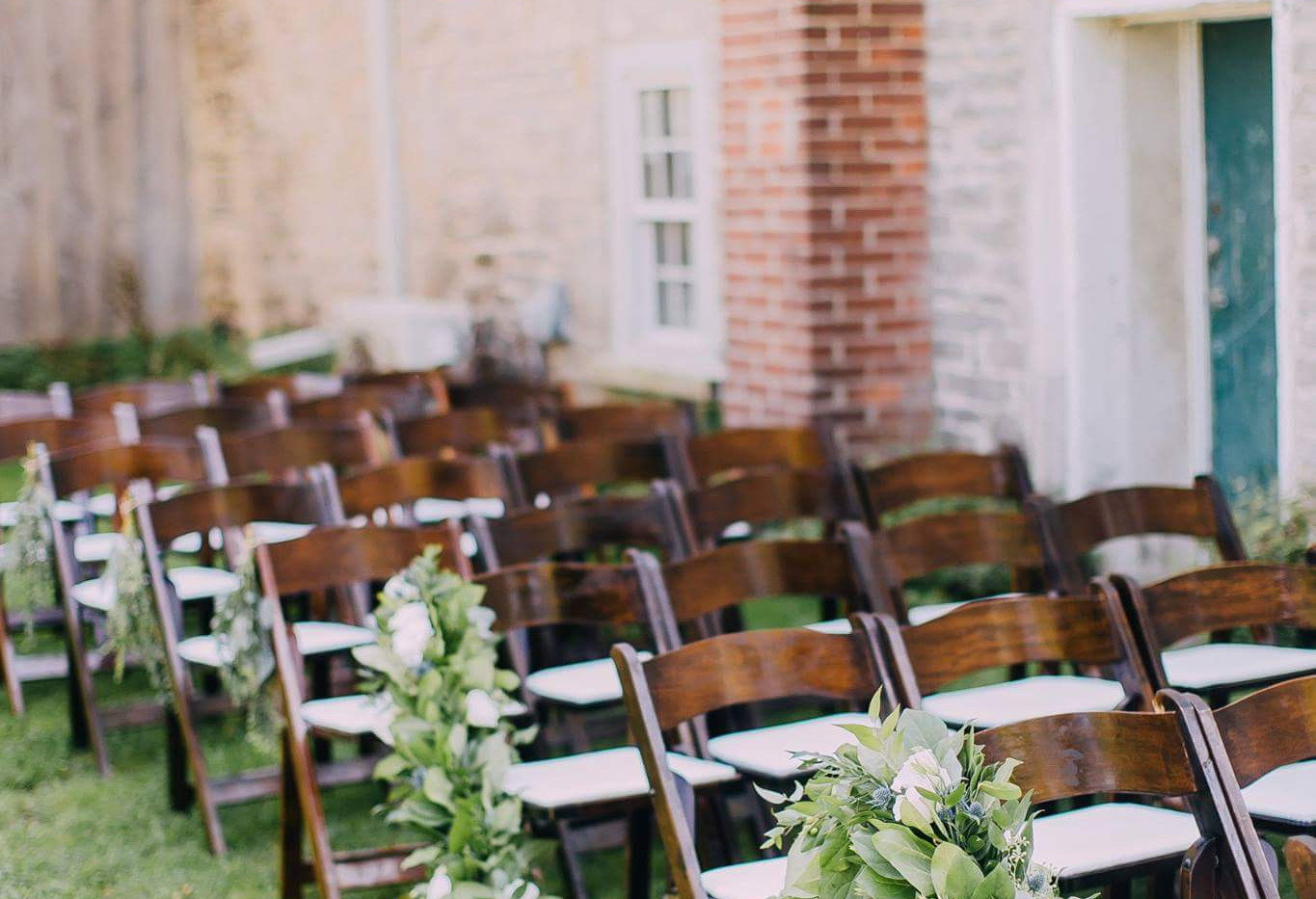 Espresso folding garden chairs at ceremony with floral and greenery garlands swagged along chairs