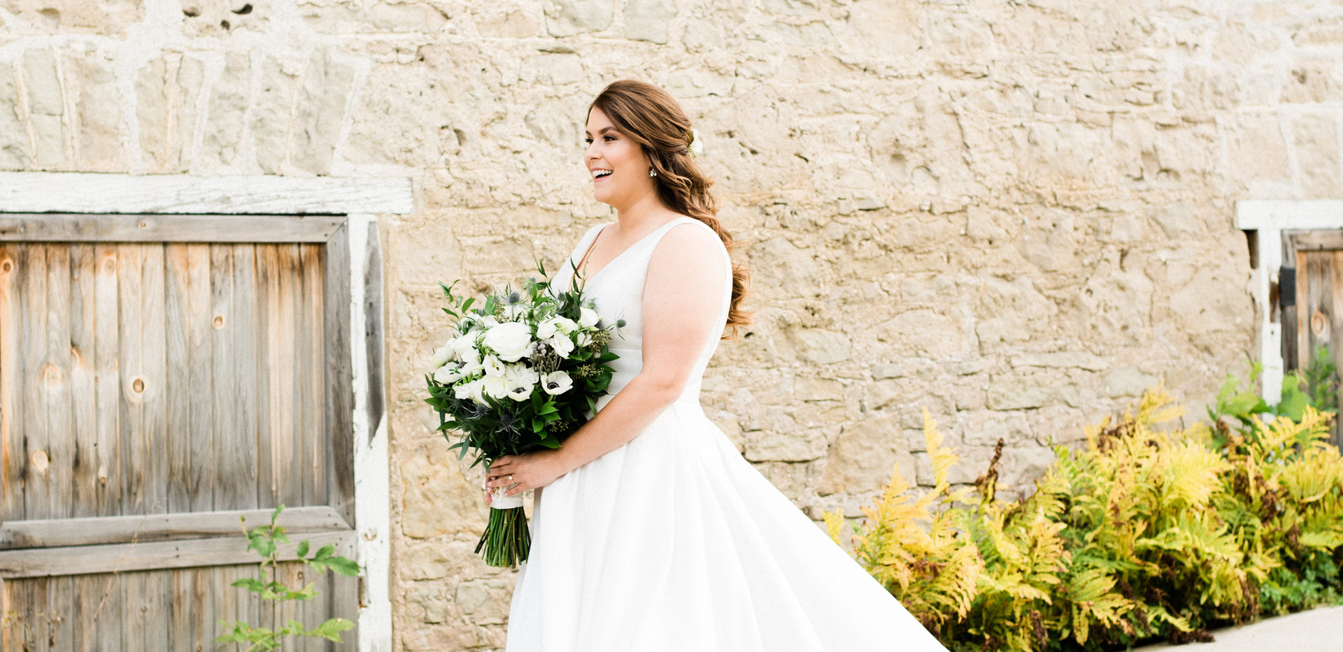 bride walking down hill next to white stone barn for first look with groom