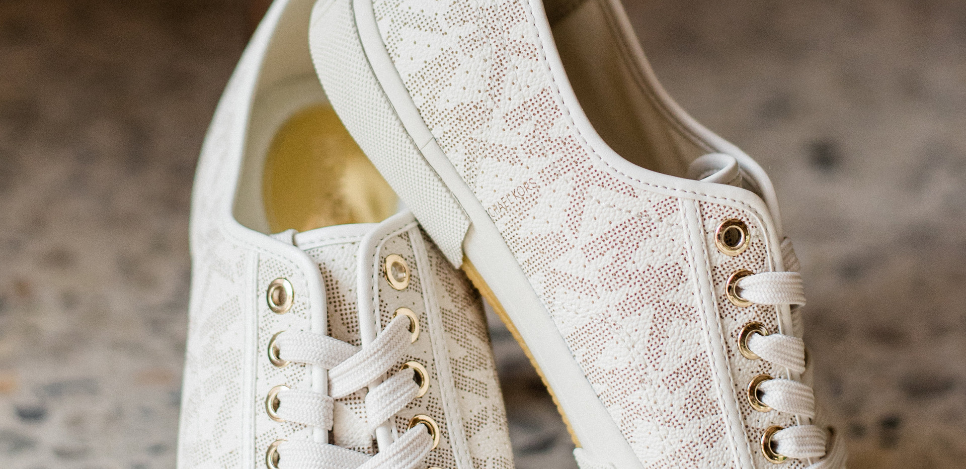 close up shot of Michael Kors bridal sneakers propped up on top of eachother