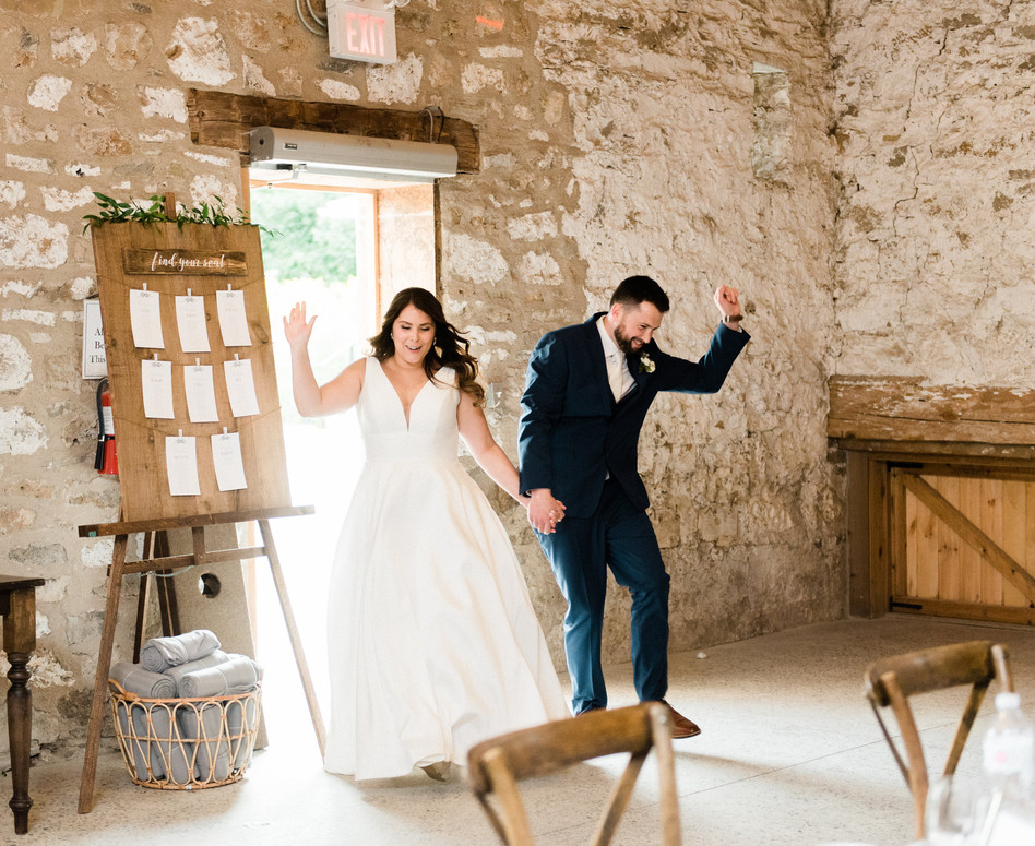 bride and groom grand entrance into white stone barn reception with seating chart next to doorway